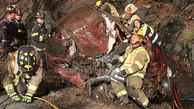 Lake Carmel and Patterson firefighters work to remove the driver from a vehicle that collided with a tractor-trailer on eastbound Interstate 84 in the town of Kent early Friday morning April 24, 2015. The driver of the car was flown from the scene by a medevac helicopter.