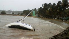 A boat lays on its side off the shore of Sainte-Anne