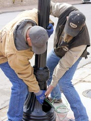 Sean Jameson, left, and Edward Laney install a light post that was found in downtown Silver City on Tuesday.