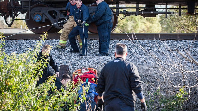Emergency responders work to transport a man and woman who were struck by a train near Ohio and Blaine Streets in Muncie Saturday, Oct. 17, 2015.  The man and woman were walking down the tracks when they were struck by the train and suffered possible serious but non life threatening injuries.
