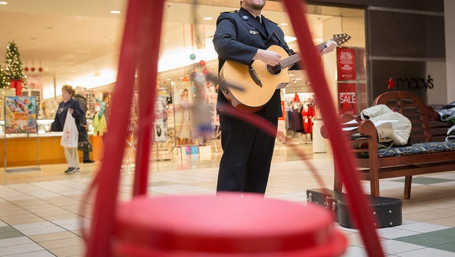 Jonathan Taube plays guitar and sings Christmas songs in front of the Macy's at the Muncie Mall during The Salvation Army's kettle season ceremony Saturday morning.