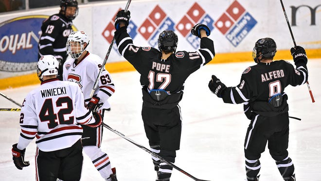 Nebraska-Omaha players David Pope (12) and Riley Alferd (9) celebrate a Nebraska-Omaha goal during the second period of Saturday's game at the Herb Brooks National Hockey Center in St. Cloud.