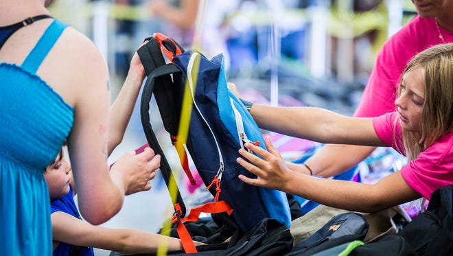Children pick out backpacks during the 2-16 Tools for School event at the Delaware County Fairgrounds Saturday morning. The event provided backpacks, school supplies and shoes for children in need.