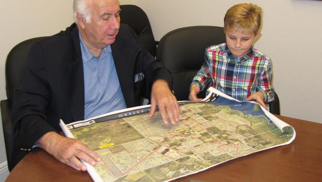 Estero Mayor Nick Batos looks over a map of the newly incorporated Village of Estero with nine-year-old Nicky Snow, who is interested in local government and geography.