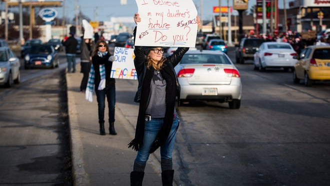 """Hundreds of teachers, students and community members gathered for the """"Save MCS"""" rally at the intersection of McGalliard Road and Wheeling Avenue Friday evening."""
