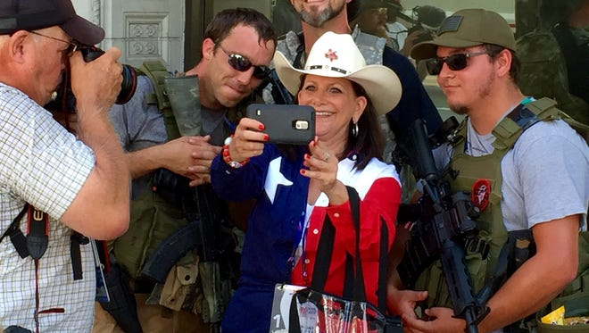 A group of men carrying firearms attracted a lot of attention at the Republican National Convention, including one woman who posed for a selfie with them.
