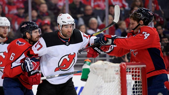 New Jersey Devils left wing Patrick Maroon (17) scuffles with Washington Capitals defenseman Michal Kempny (6) and defenseman John Carlson (74) during the first period of an NHL hockey game Saturday, April 7, 2018, in Washington.