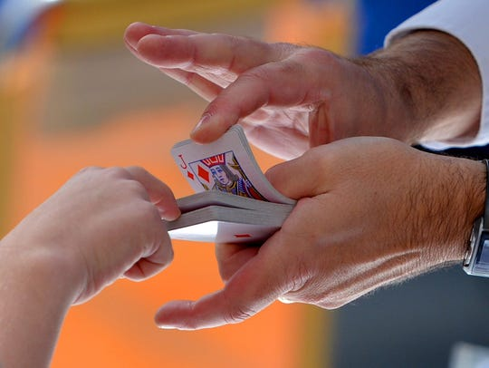Magician Brian Bence performs a card trick during the