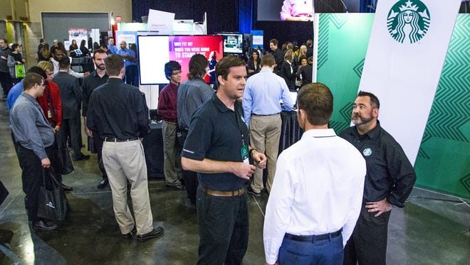 Prospective employers and employees mingle at the Starbucks booth at the 100,000 Opportunities Initiative in Phoenix on Friday.