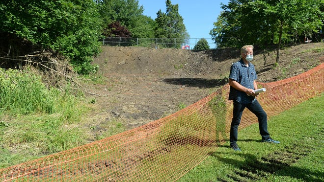 Vern Peterson, executive director of the Lake Erie Arboretum at Frontier Park, stands at the site of three 40-foot slides under construction at the park.