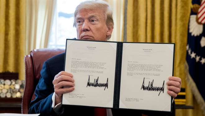 President Trump holds up a bill after signing it in the Oval Office of the White House in Washington, D.C,  on Dec. 22, 2017. Trump signed the tax bill, a continuing resolution to fund the government, and a missile defense bill before leaving to spend Christmas in Mar-a-Lago, Florida.