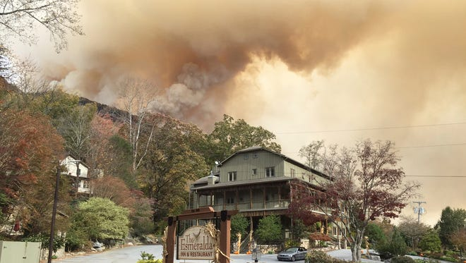 In this photo made available by Don Cason, shows his business, The Esmeralda Inn and Restaurant, which was evacuated due to the proximity of wildfires, Friday, Nov. 11, 2016 in Lake Lure, N.C. The shroud of smoke is making a dent in the tourism economy _ which thrives during the fall season in much of the affected area _ in some part, but Lake Lure could be taking the most concentrated hit.