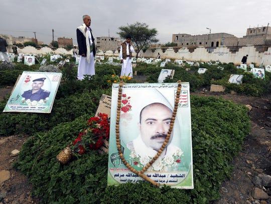 Yemeni people stand among the graves of pro-Houthi