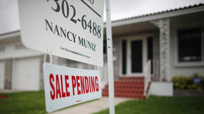 "A ""Sale Pending"" sign is seen in front of a home in Miami."