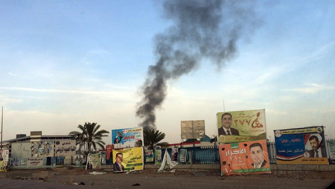Smoke rises above campaign posters Friday after a series of bombs that exploded at a campaign rally for a Shiite group in Baghdad, Iraq.