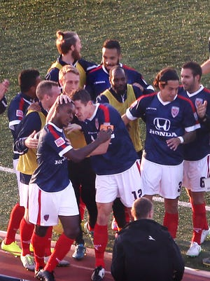 Indy Eleven forward Brian Brown (foreground) is swarmed by teammates after he scored the game's first goal, April 11, 2015.