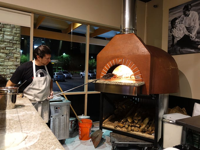 Chef and owner Fabio Ceschetti tends the wood burning