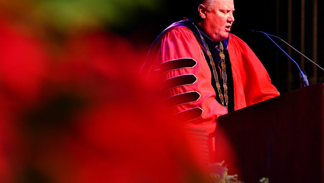 Eastern Florida State College held two commencement ceremonies Thursday for their Fall graduates. Dr. Jim Richey, president of EFSC, addresses the students with Christmas arangements framing the stage.