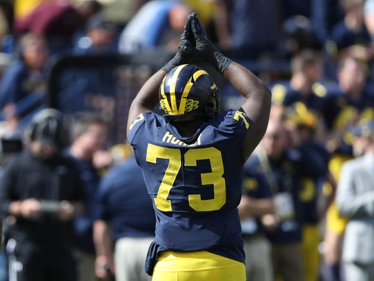 Michigan's Maurice Hurst signals for a safety in the