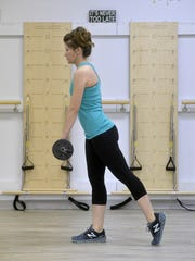 Stand on one leg and hold a dumbbell in the opposite hand. Keep your back and arm straight, hinge at your hip and bend forward toward the floor, keeping your weight-bearing knee bent. As you hinge, allow your non-weight bearing leg to elevate upward so it remains in a straight line  with your torso, and do not allow your non-weight bearing leg to elevate upward so it remains in a straight line with your torso, and do not allow your lower back to round out.