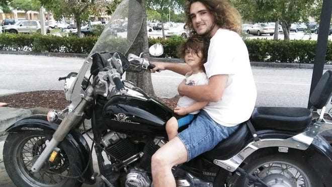 Travis William Fletcher sits with his son, Travis Reed Fletcher, on a motorcycle in an undated photo. The 29-year-old died of a fentanyl overdose while in custody at the Palm Beach County jail in March, according to a recently released report.