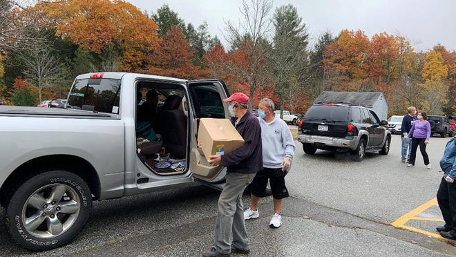 Volunteers hand out boxes of food at Gardner Middle School on the last day of the federal Farmers to Families food program on Oct. 23.