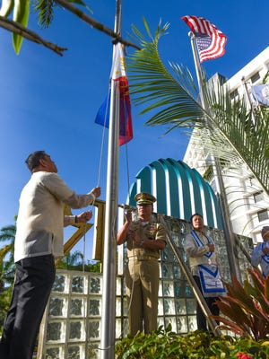 Armed Forces of the Philippines' Rear Adm. Samuel Felix, facing, is assisted by Joel Dreyfus, Guam Reef & Olive Spa Resort assitant purchasing agent, in the hoisting of the Philippine flag during the 12th annual flag raising ceremony at the Guam Reef & Olive Spa Resort in Tumon on Tuesday, June 12, 2018. The event was held by the hotel in celebration of the 120th anniversary of the proclamation of Philippine independence.