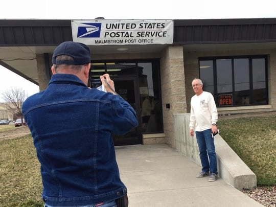 Wayne Olson snaps a picture of Gary Splittberger as he visits the post office at Malmstrom Air Force Base. He's now been to all the active post offices in Montana.