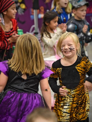 Macey Lingl smiles while dancing to the Hokey Pokey with friends during the Kids & Parents Expo Saturday, Oct. 28, at the River's Edge Convention Center in St. Cloud.