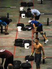 Participants compete in the Iron Bar event during the