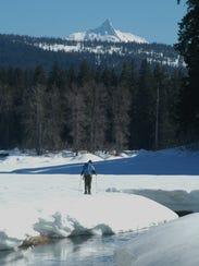 Scott Hovis snowshoes at Fish Lake with Mount Washington