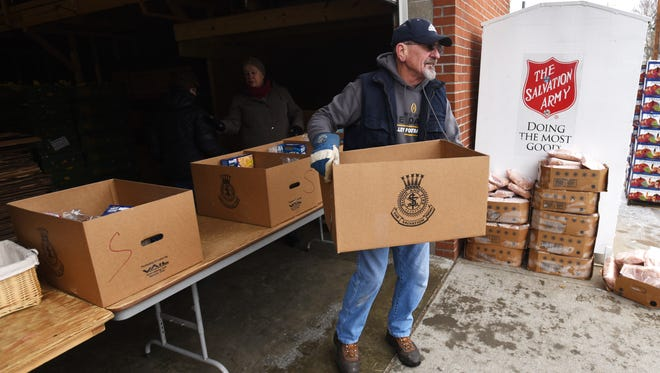 Dave Pfeifer carries a box to a waiting car during the first of two Salvation Army distribution days this month.