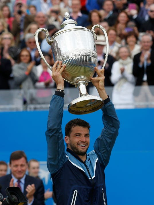 Grigor Dimitrov of Bulgaria holds up the trophy after his win against Feliciano Lopez of Spain at the end of their Queen's Club grass court championships singles final tennis match in London, Sunday, June 15, 2014. (AP Photo/Sang Tan)