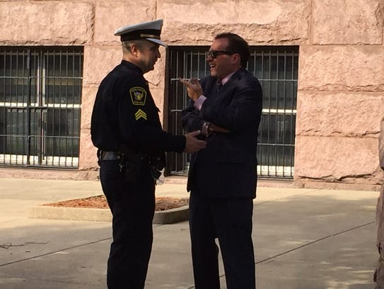 Mayor John Cranley and police union president Dan Hils talk before a 2016 press conference promoting Cranley's plan to give raises to city workers, including police officers.