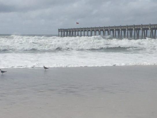 Waves crash onto the beach at Pensacola Beach as Tropical