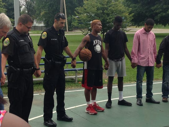 Muncie police officers hold hands with members of Muncie's