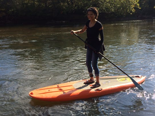 Karen Chávez paddles down the French Broad River on