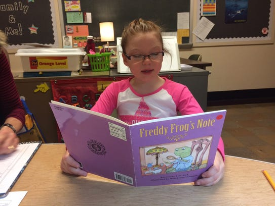 First-grader Tessa Zoch enjoys a book during her one-on-one