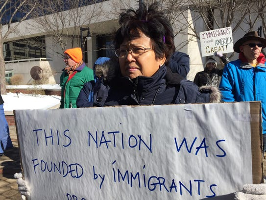 Tanua Djanegara, of Wilmington, holds a sign during
