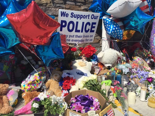 Flowers, balloons, teddy bear and other items are left