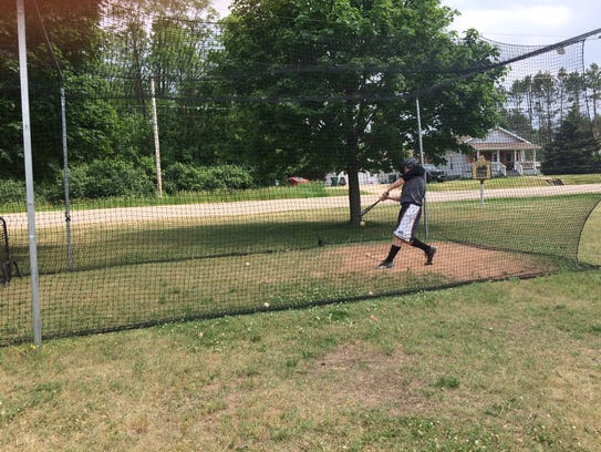 Ethan Olson takes some swings in the batting cage Monday