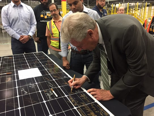 U.S. Rep. Frank Pallone Jr. signs a solar panel at