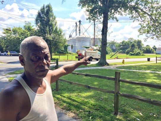 Ronald Corbin points to the fallen utility pole and