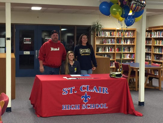 Alexis Churchill smiles with her parents at a ceremony