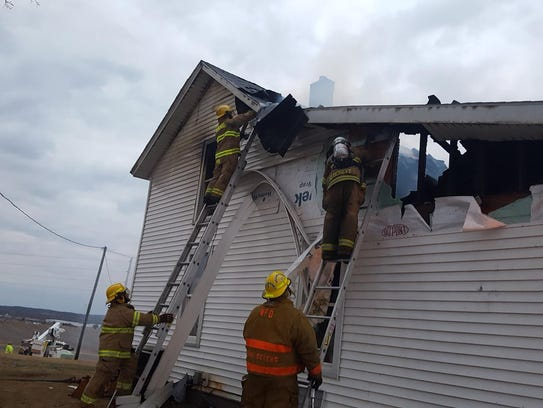 Firefighters attack a blaze during a house fire in