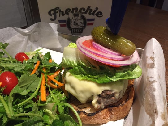 A burger from Frenchie Fresh, with a salad on the side.