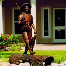 The large statue is of a boy walking barefoot, holding a fishing pole over his right shoulder and a string of fish in his left hand.