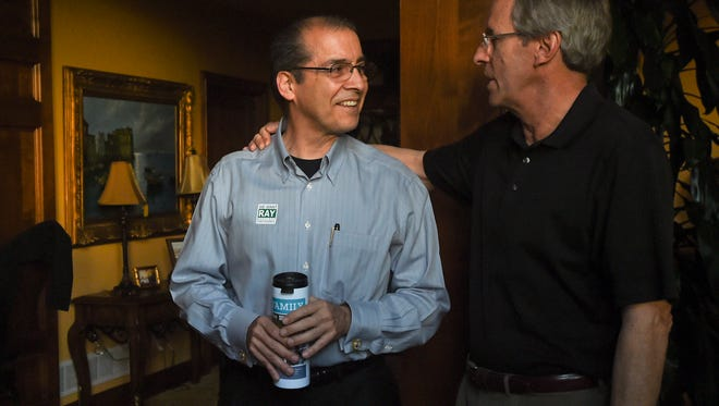 Ray Martinez speaks to Terry Danielson, right, Tuesday, April 7, 2015 at Martinez's election party in Fort Collins, CO. Martinez and Danielson have known each other since junior high, Danielson said.