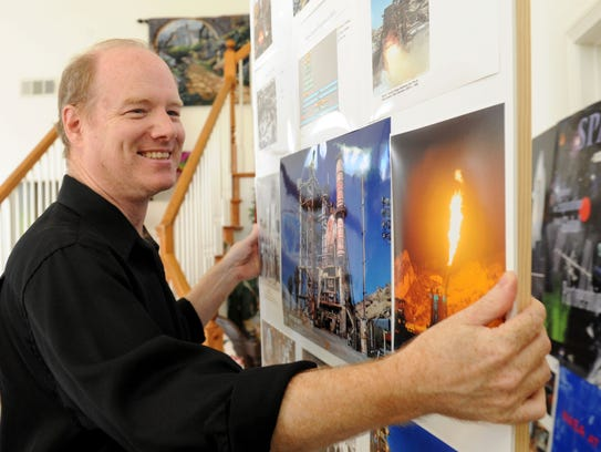 Mark Kidd helps move boards with photos of NASA and