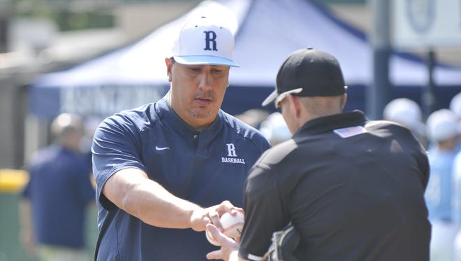 Redwood coach Dan Hydash hands over the game balls to an umpire before the Rangers' semifinal game against Bakersfield in the Central Section Division II postseason.